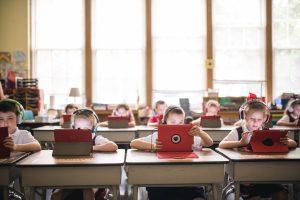 Children at desks using iPads